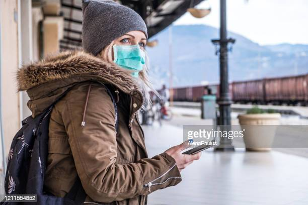 caucasian woman waring face mask on the station - coronavirus winter stock pictures, royalty-free photos & images