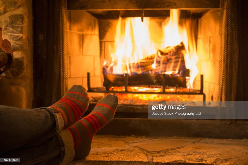 Caucasian woman warming feet near fireplace : Stock Photo