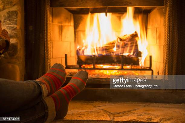 Caucasian woman warming feet near fireplace