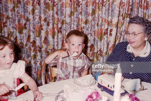 Caucasian woman watching grandson and granddaughter eating cake