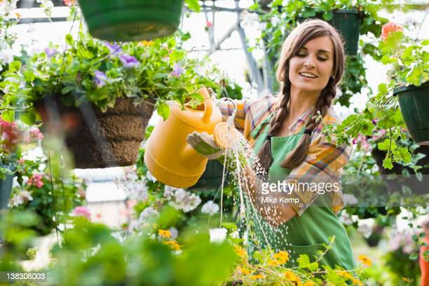 Caucasian woman watering plants in nursery