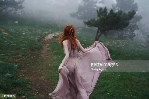 Caucasian woman wearing a dress in field