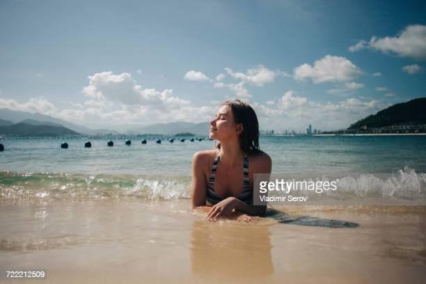 Caucasian woman wearing bikini laying in waves on beach
