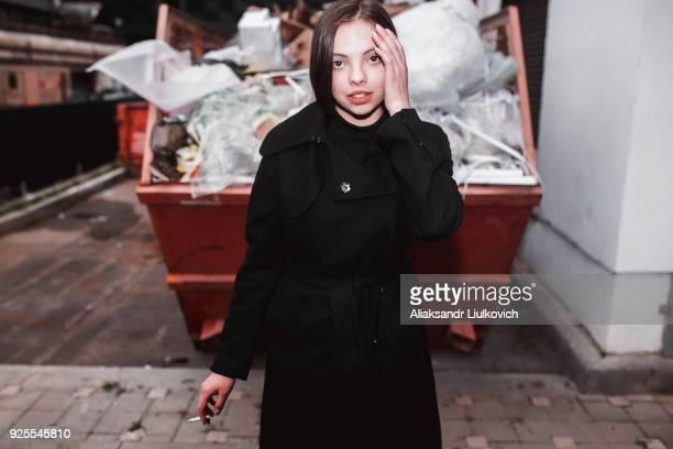 caucasian woman wearing black coat smoking cigarette near dumpster - beautiful women smoking cigarettes stock pictures, royalty-free photos & images