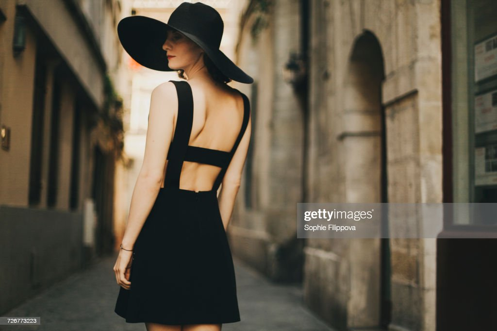 Caucasian woman wearing black dress and sun hat in street : Photo