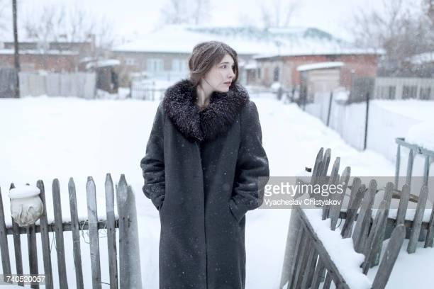 Caucasian woman wearing coat in winter near fence