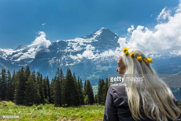 Caucasian woman wearing crown of flowers near mountains