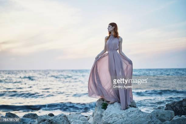 Caucasian woman wearing dress on rocks near ocean