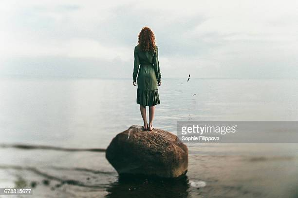 caucasian woman wearing dress standing on rock at beach - jeune fille rousse photos et images de collection