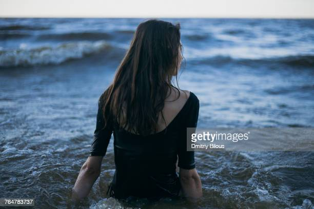 Caucasian woman wearing dress wading in ocean