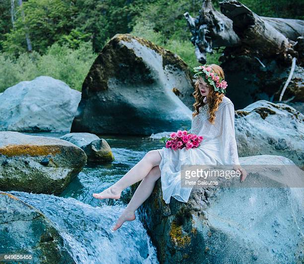 Caucasian woman wearing flower crown on rock at river waterfall