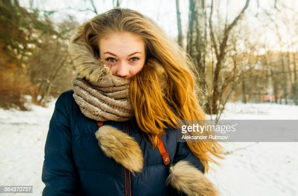 Caucasian woman wearing fur hood and coat in snowy field