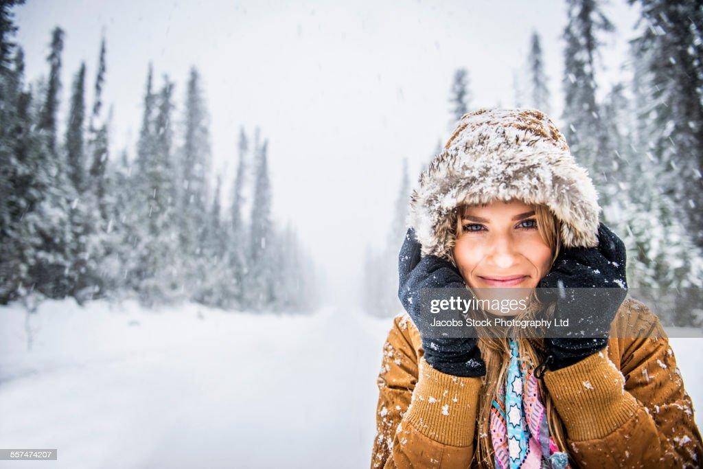 Caucasian woman wearing fur parka hood in snow : Stock Photo