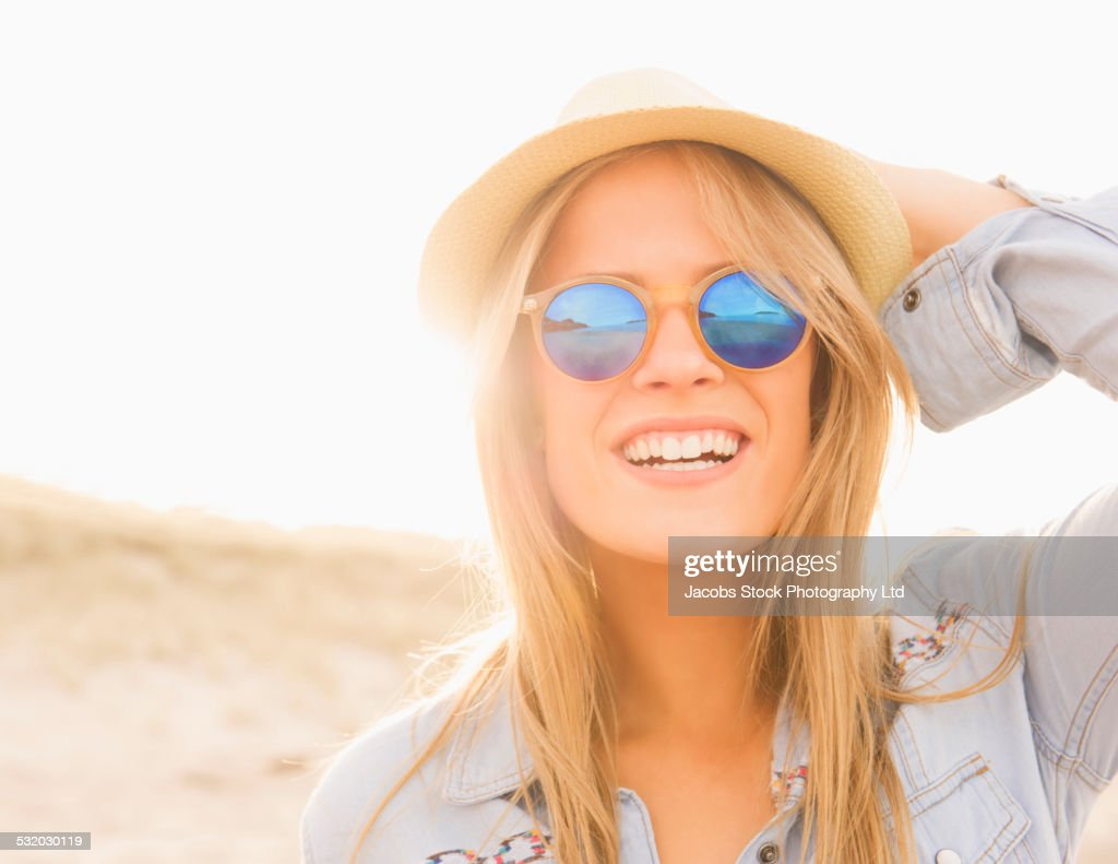 Caucasian woman wearing hat and sunglasses on beach : Stock Photo