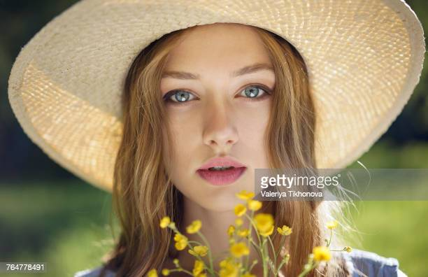 caucasian woman wearing hat holding wildflowers - produit de beauté photos et images de collection