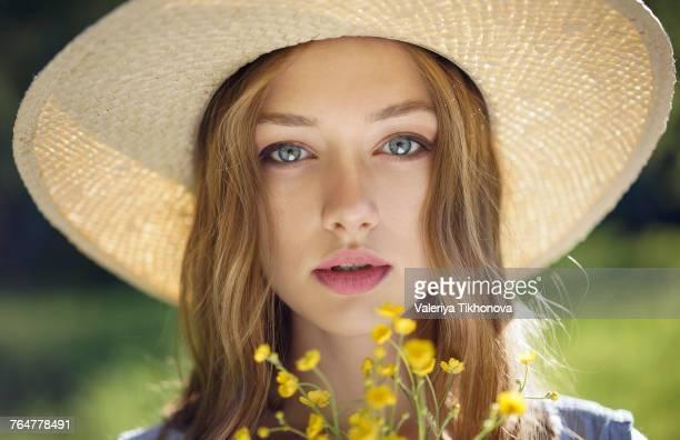 Caucasian woman wearing hat holding wildflowers