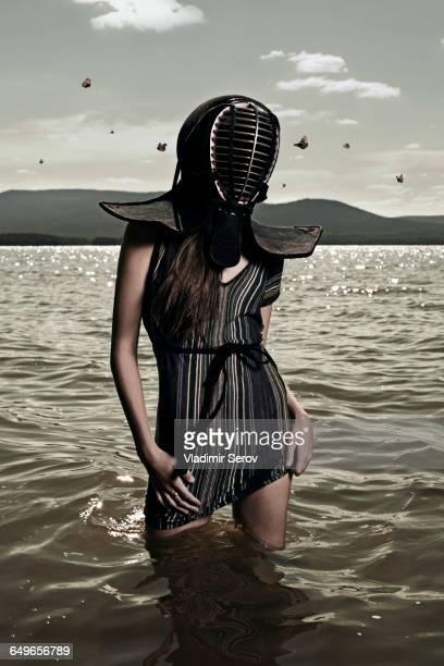 Caucasian woman wearing mask in lake