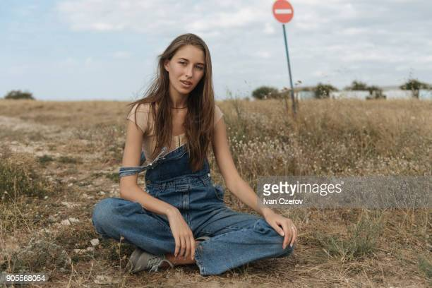 Caucasian woman wearing overalls sitting in rocky field