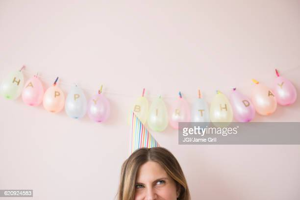 Caucasian woman wearing party hat at birthday