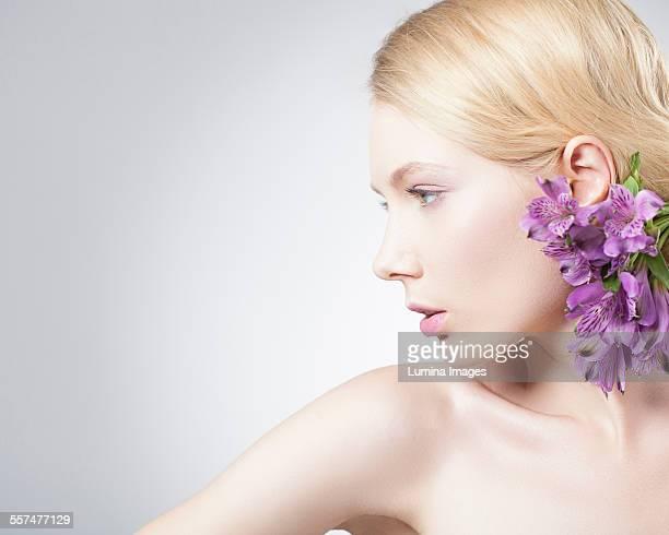 Caucasian woman wearing purple flowers in hair