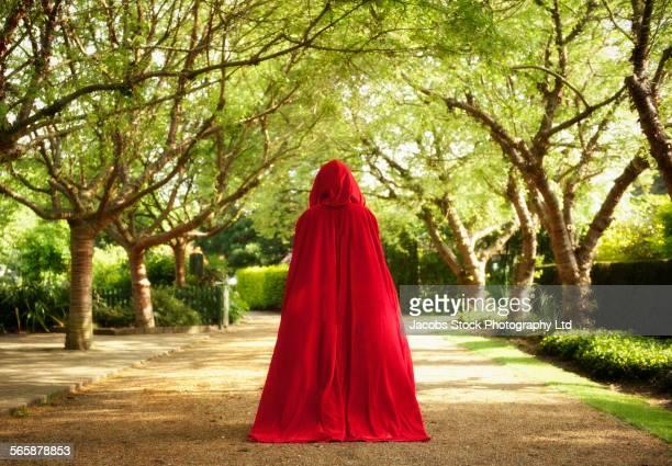 caucasian woman wearing red cape in garden - ケープ ストックフォトと画像