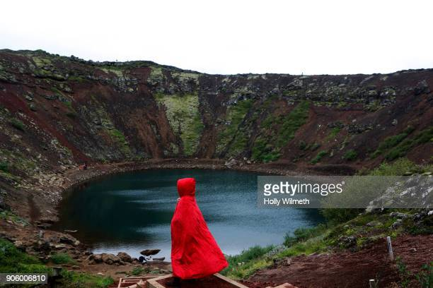 Caucasian woman wearing red robe at volcano lake