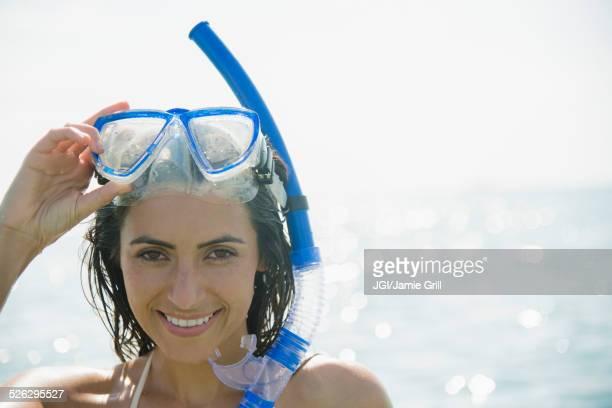 Caucasian woman wearing snorkel and mask in ocean