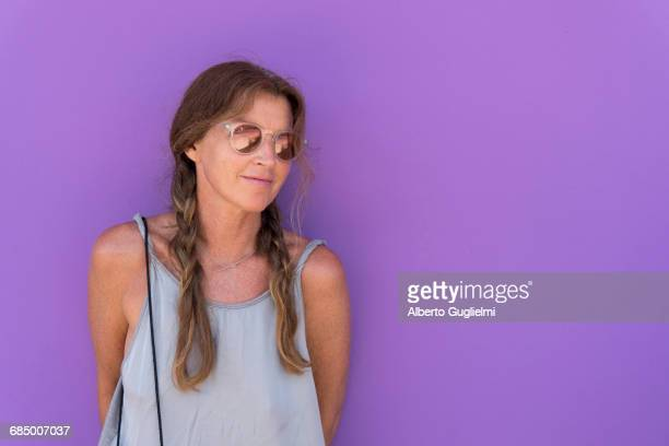 Caucasian woman wearing sunglasses leaning on purple wall