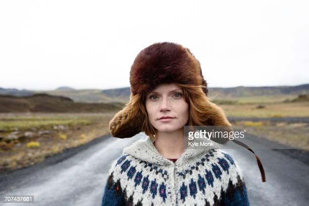 caucasian woman wearing sweater and fur hat in middle of road - fur hat stock photos and pictures
