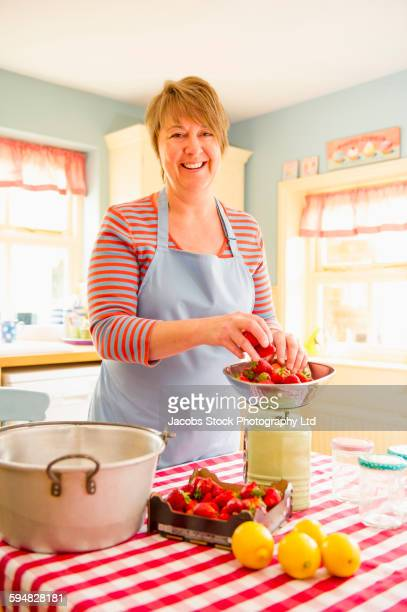 Caucasian woman weighing fruit in kitchen
