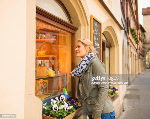 Caucasian woman window shopping in city