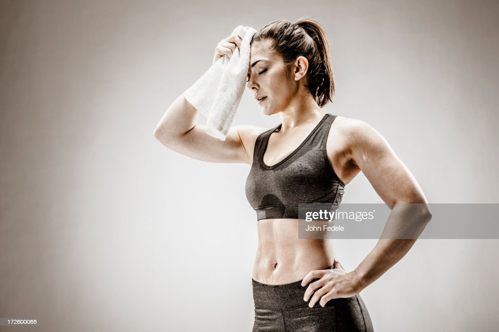 Caucasian woman wiping sweat from forehead : Stock Photo