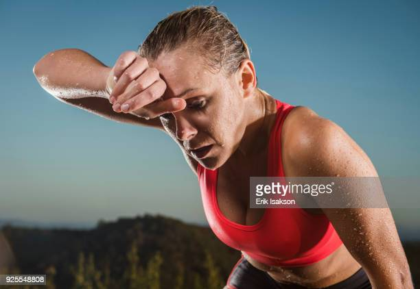 caucasian woman wiping sweat from forehead - sforzo foto e immagini stock