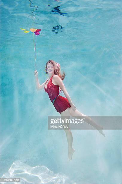 Caucasian woman with balloons underwater