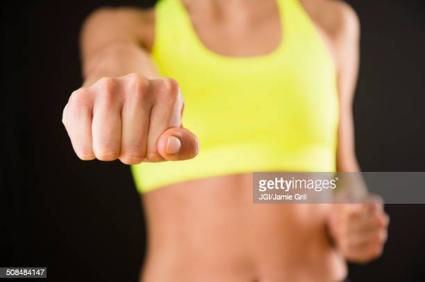 Caucasian woman with bare stomach punching