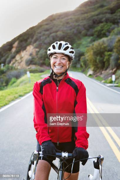 Caucasian woman with bicycle smiling on remote mountain road