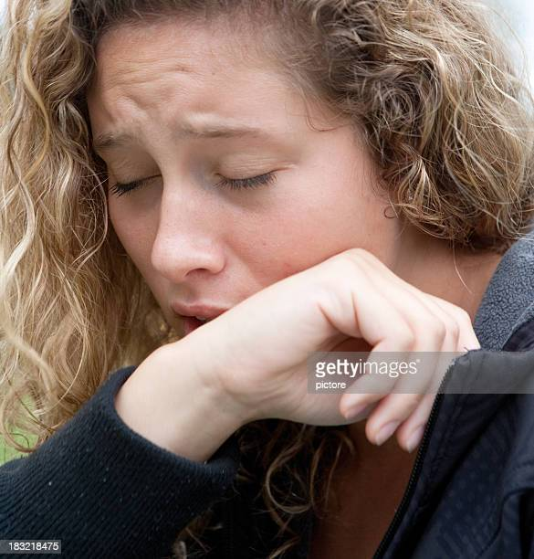 Caucasian woman with blond hair coughs or sneezes