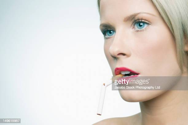 Caucasian woman with broken cigarette in her mouth