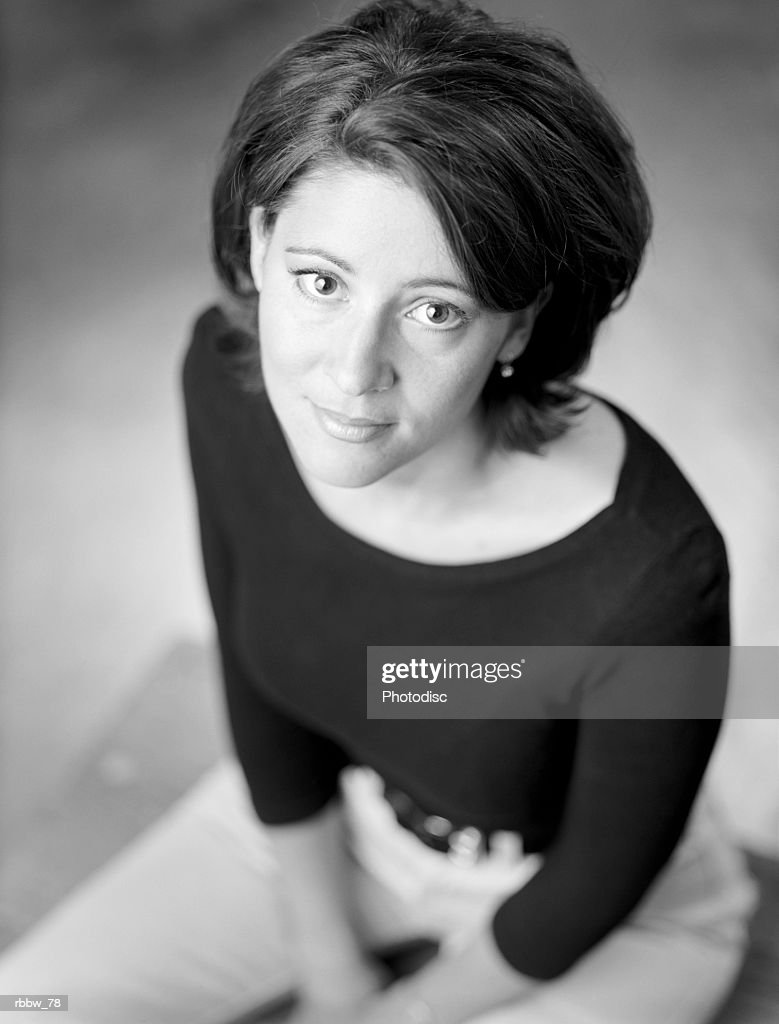 A caucasian woman with dark hair sits patiently looking up : Stockfoto