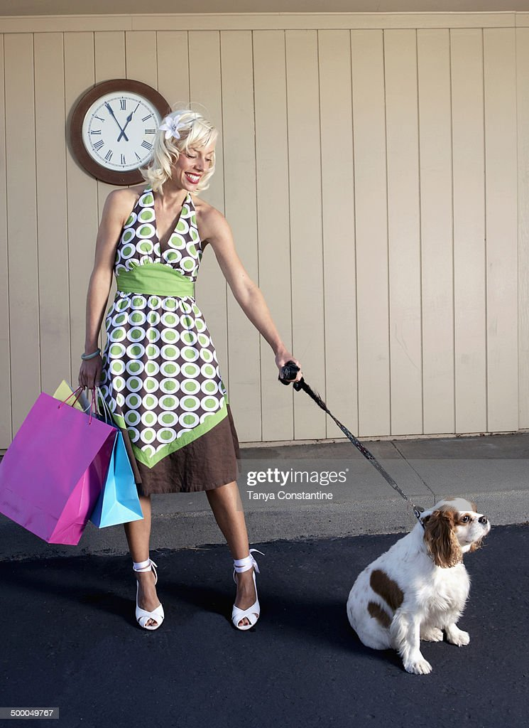 Caucasian woman with dog on sidewalk : Stock Photo