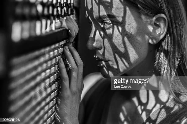 caucasian woman with freckles leaning on window - freckle stock photos and pictures