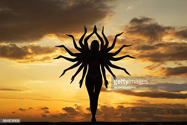 Caucasian woman with many arms under sunset sky