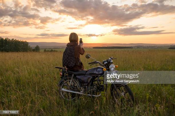 Caucasian woman with motorcycle in field photographing sunset