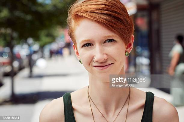 caucasian woman with nose ring smiling on city sidewalk - ohrring stock-fotos und bilder