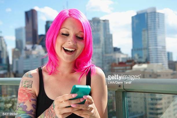 Caucasian woman with pink hair and tattoos using cell phone on urban rooftop