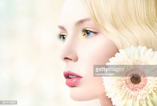 Caucasian woman with pink lipstick wearing white flower