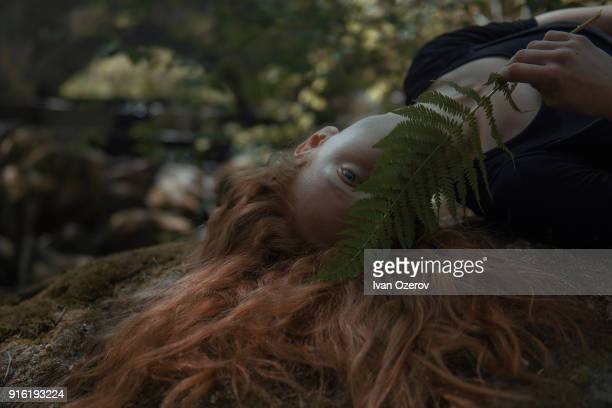 Caucasian woman with red hair hiding face behind leaf