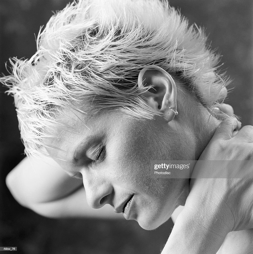 A caucasian woman with short blonde hair holds her neck : Stockfoto