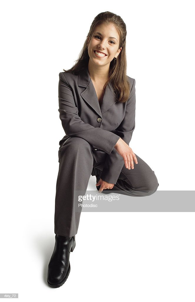 caucasian woman with straight long brown hair wearing a gray suit and black boots smiles at the camera as she kneels : Foto de stock