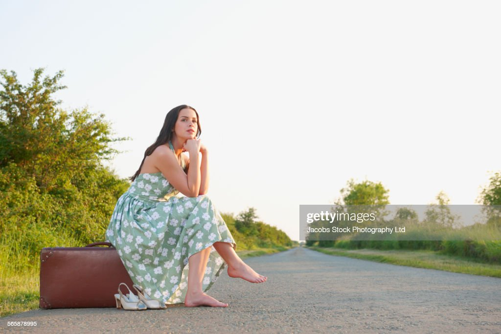 Caucasian woman with suitcase waiting on rural road : Stock Photo